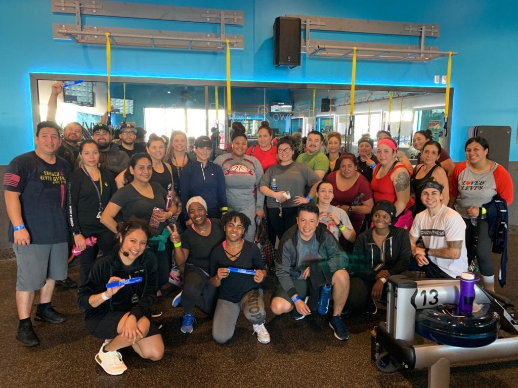A group of Team Training members posing for a photo in their best 90's outfits at the Cudahy CA Chuze Fitness location