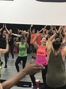 Instructor, Bettly Layman, in front of the Zumba Group Exercise class in an orange and pink Zumba shirt with her hands up in the air.