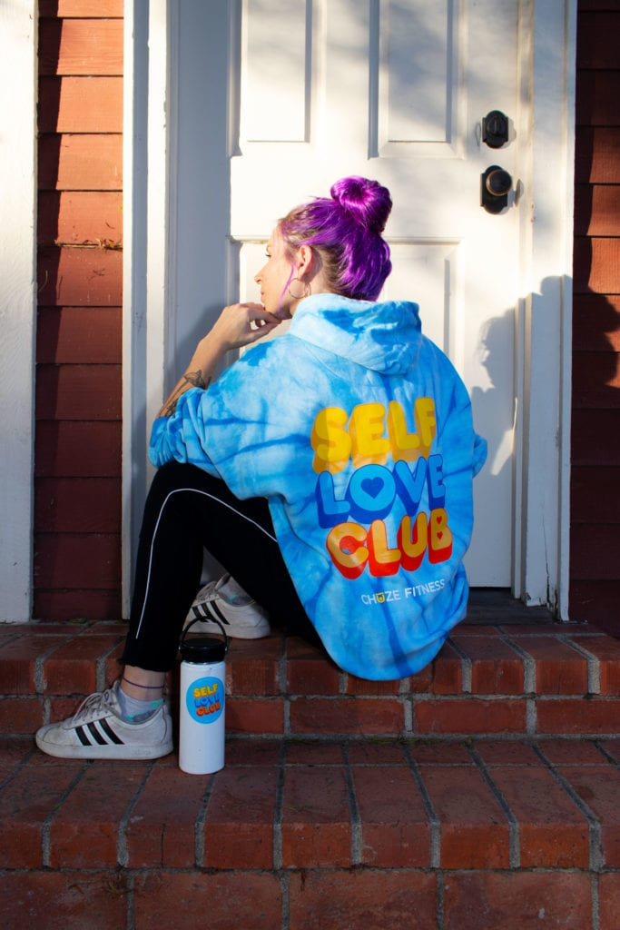 """Woman in sitting in front of a doorway with our blue """"Self Love Club"""" hoodie and a water bottle covered in our Self-Care Sticker Pack"""