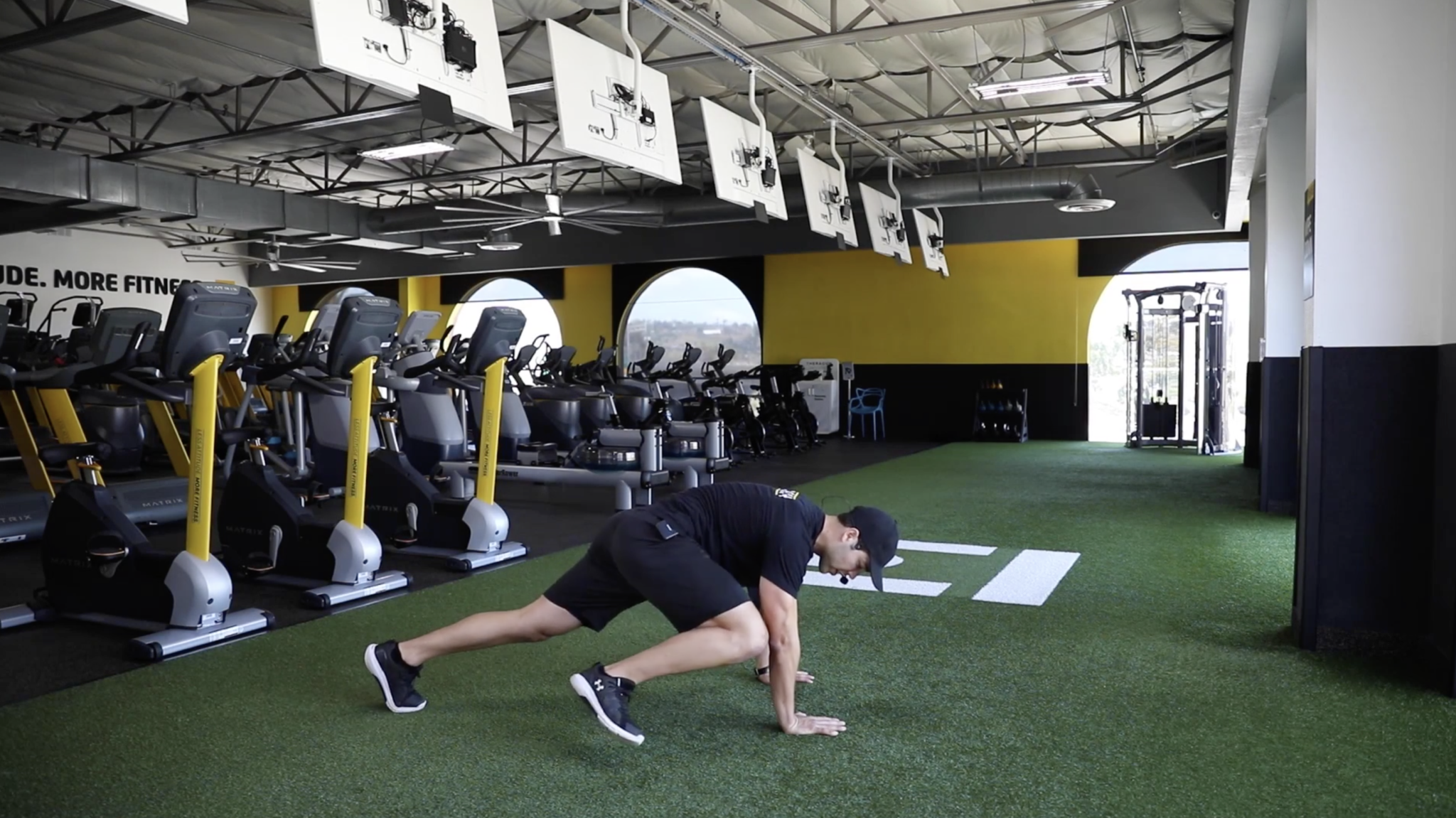 Coach Anthony, on iChuze Fitness, showing the Spiderman plank with one knee going toward the same side's elbow in a plank position