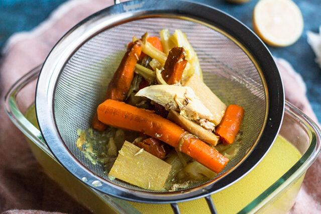 straining vegetables for ginger turmeric chicken soup