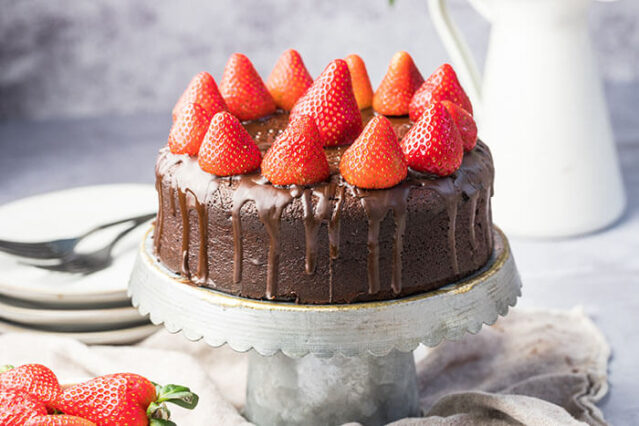gluten-free chocolate cake recipe with strawberries on a cake plate