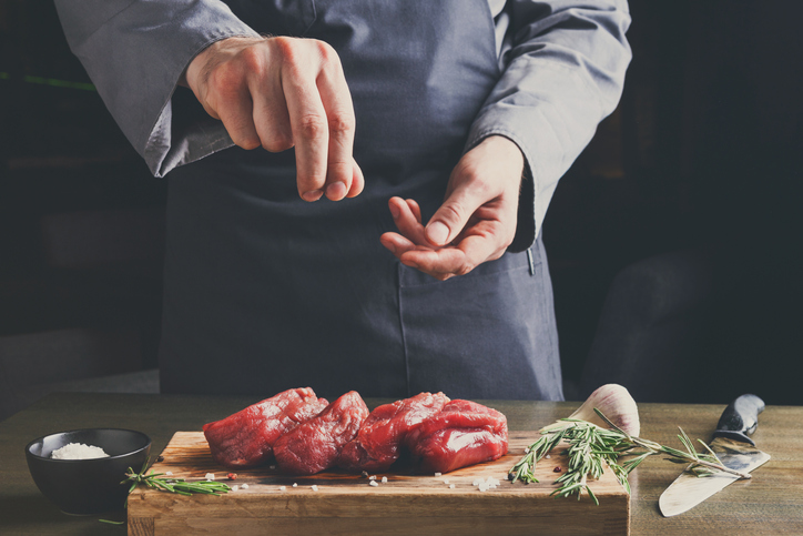 Chef seasoning filet mignon on wooden board at restaurant kitche