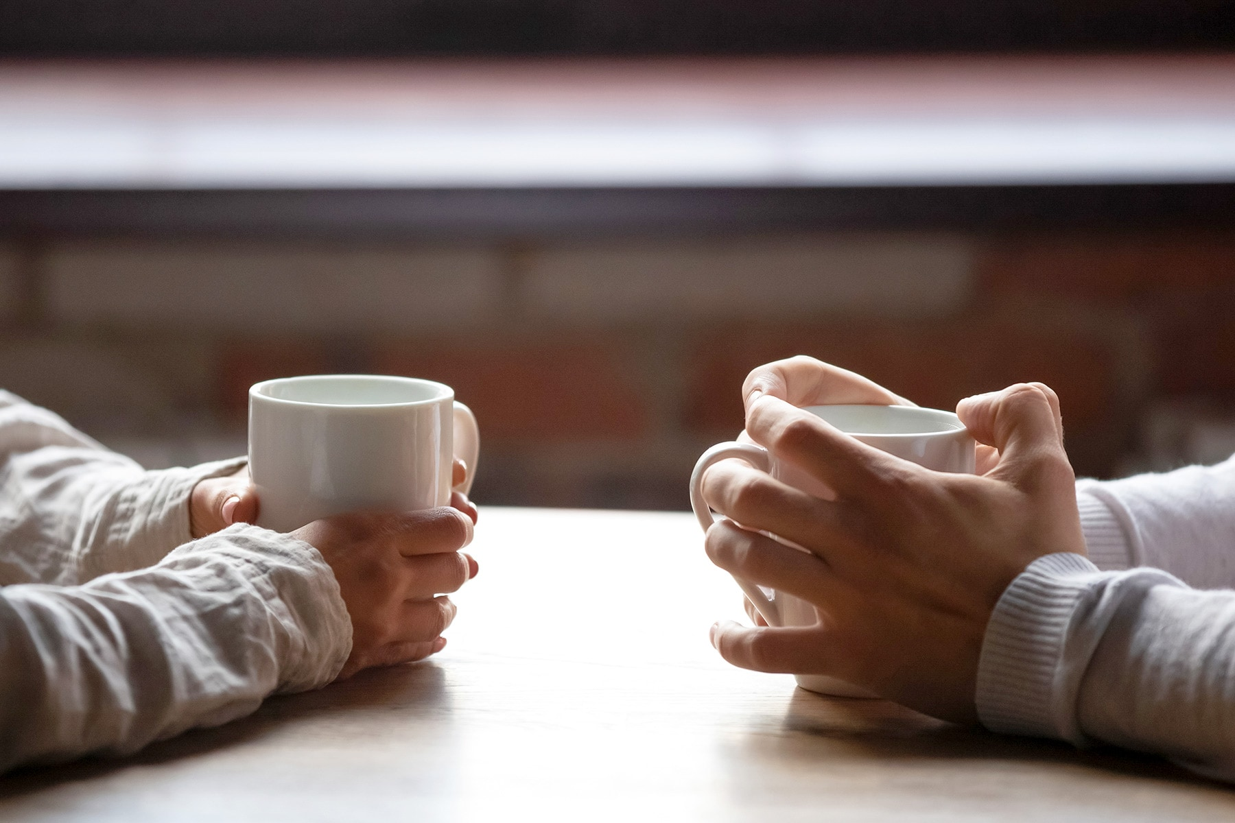 photo of hands holding cups of coffee