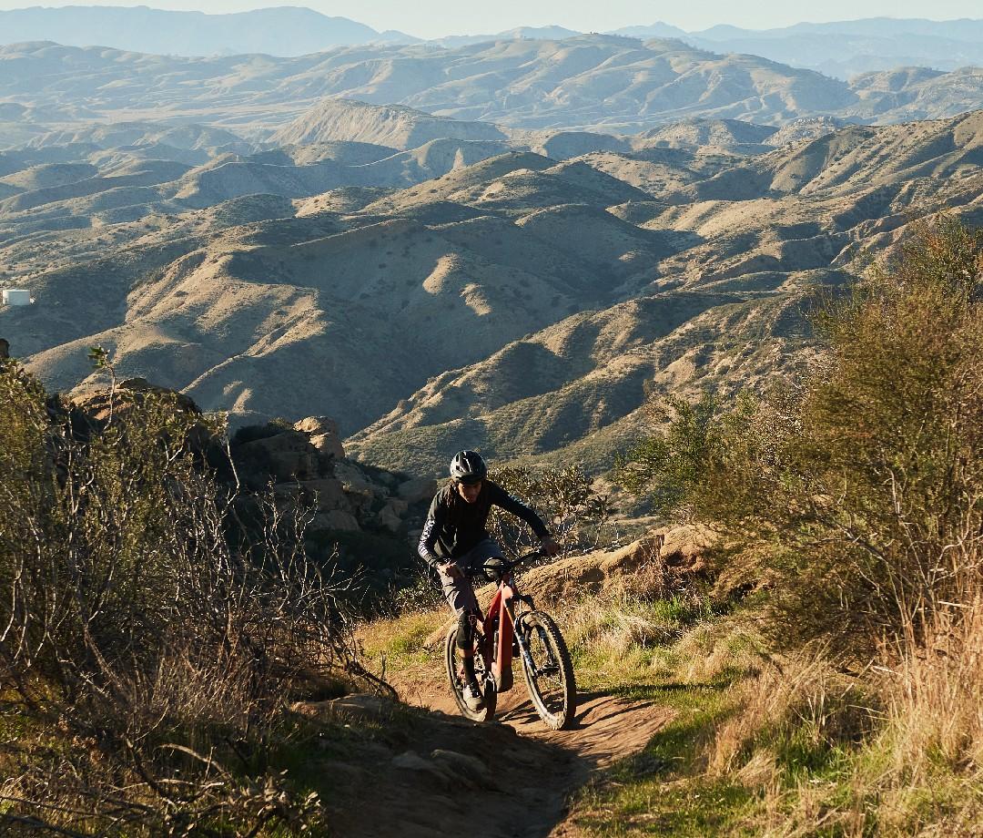 Mountain biker riding up hilly mountain
