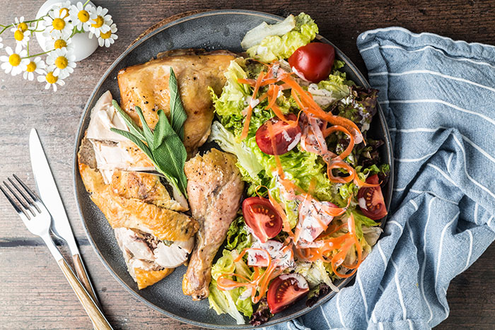 roasted spatchcock chicken recipe on a platter with salad